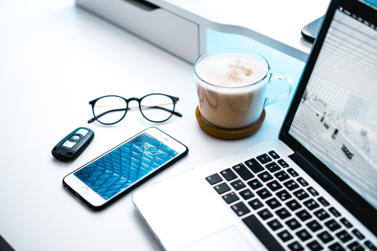 a desk with a mobile phone, spectacles, cup of coffee and laptop