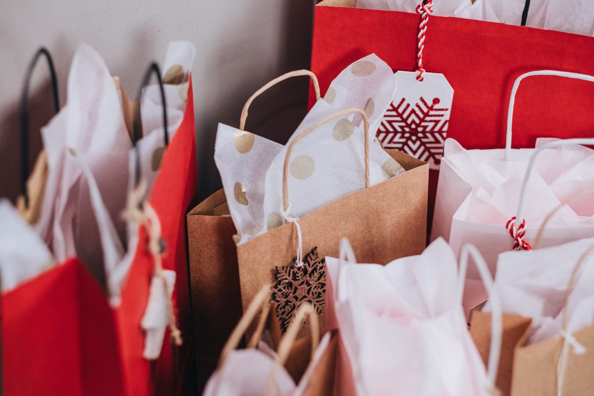 an array of shopping bags with tissue paper grouped together on the floor