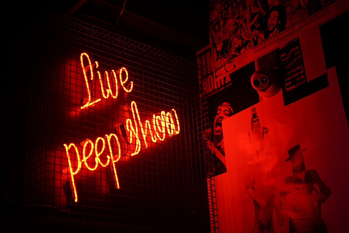 """a neon sign tilted on the wall stating """"live peep show"""""""