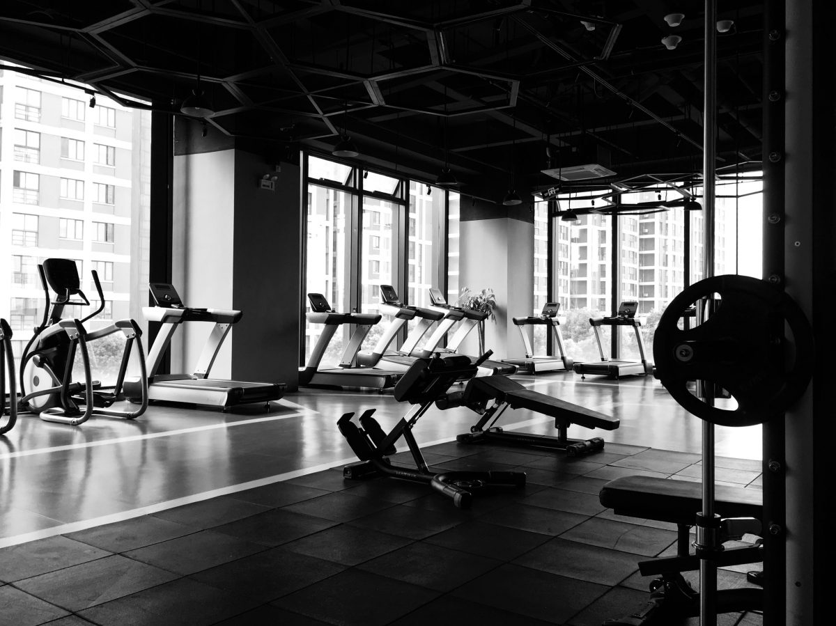 an empty gym with machines placed next to the windows