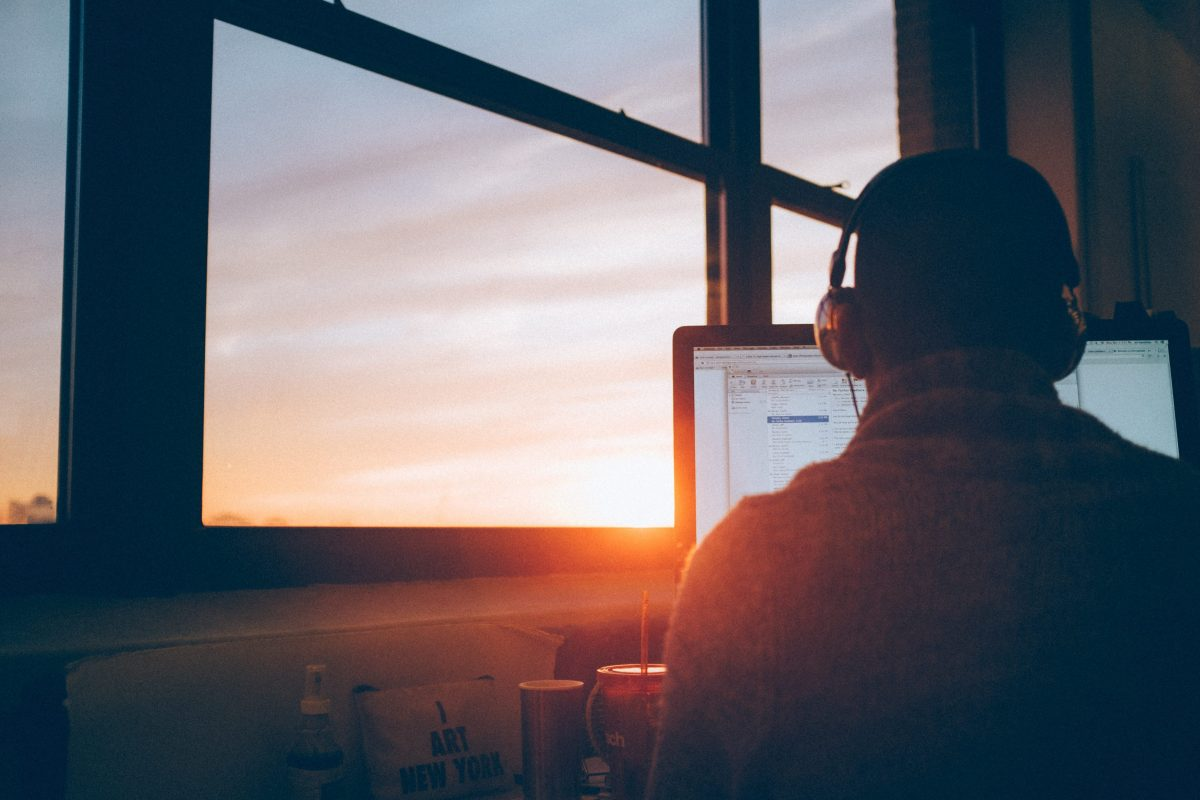 a man sitting with headphones on, at a window, facing a computer screen