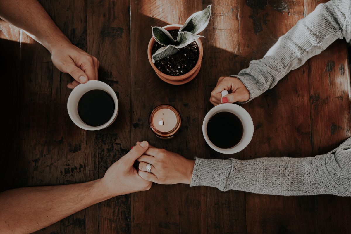 a couple holoding hands across a table, whilst holding cups of coffee