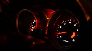 car dashboard at night showing the speedometers
