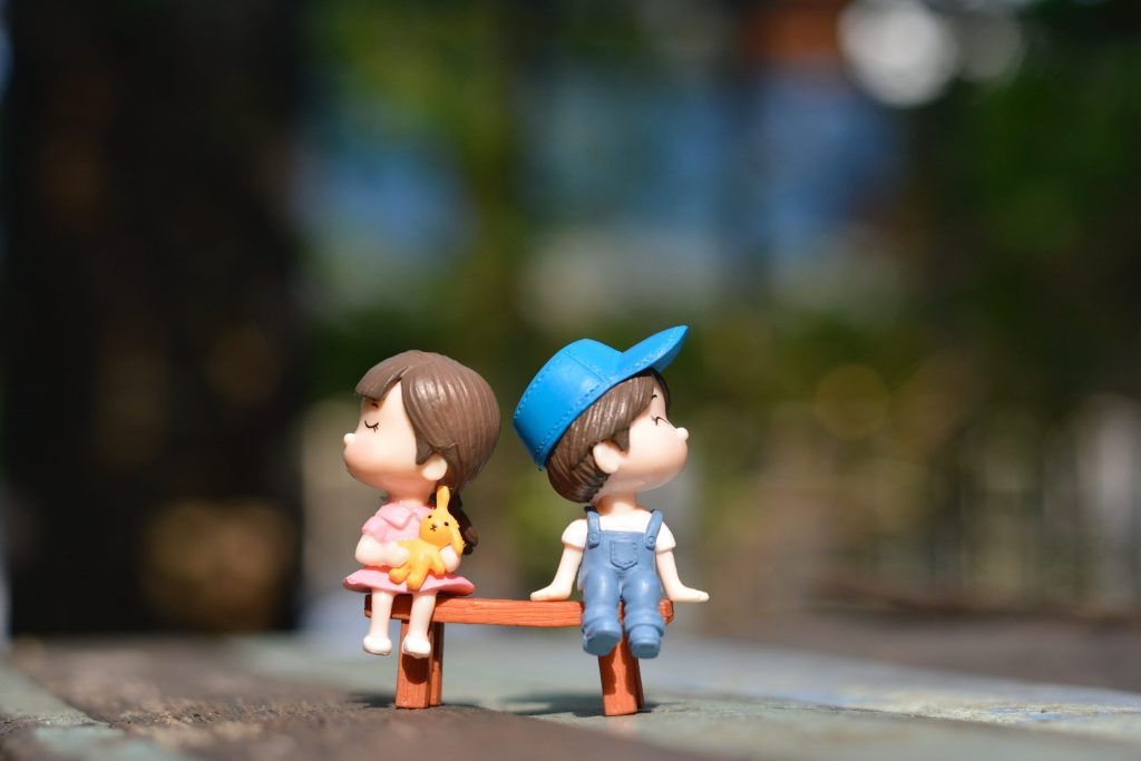 toy boy and girl, sitting on a bench, facing opposite direction