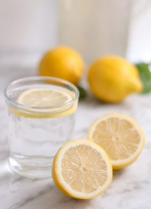 glass of water, with cut lemons