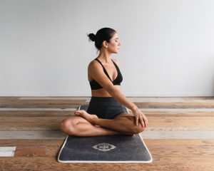 woman sitting in a yoga pose on wooden floor