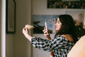 woman poses with food in her hand, taking a photo with a smartphone