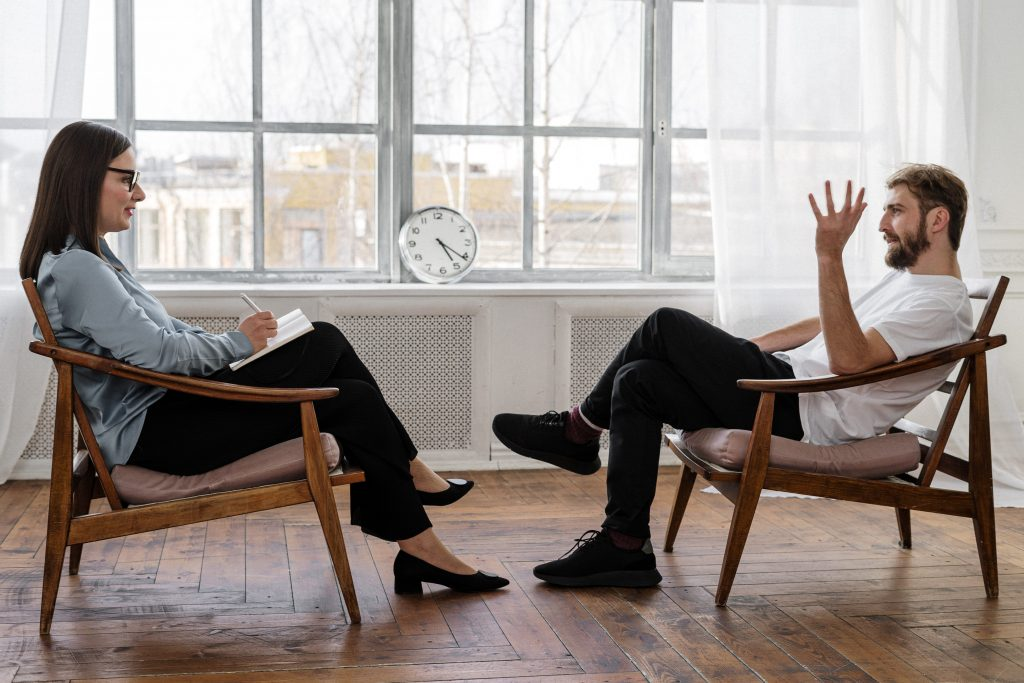 man and woman sitting on chairs, talking in counselling