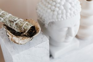 sage smmudge stick in a bowl on a marble shelf next to buddha head