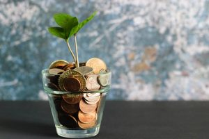 glass of coins with a small plant growing out the top