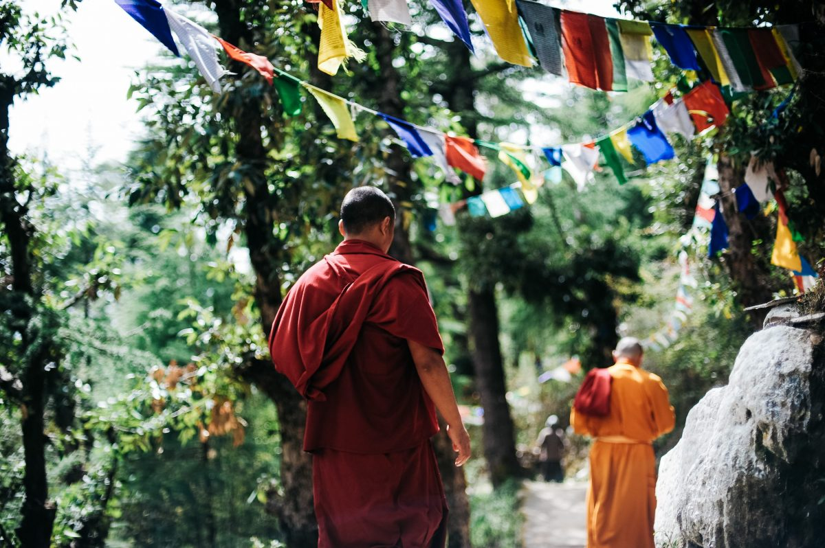 monks walk through trees with banners wafting in the wind