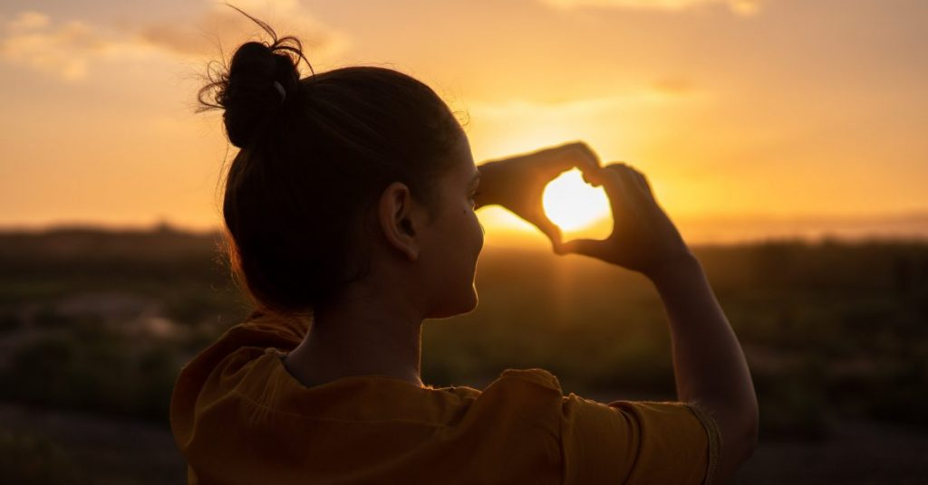 Person holding the sun in a heart