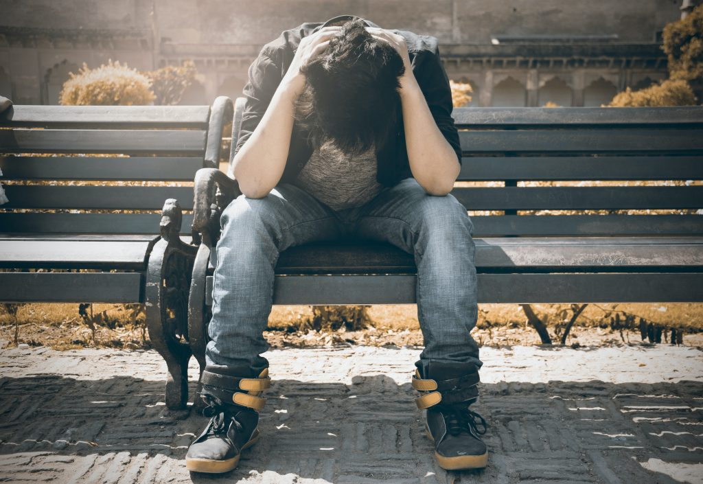 Man stressed on a park bench