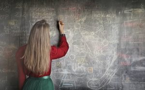 Woman writing complex equations on a blackboard.