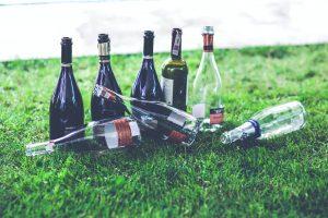 6 empty wine bottles on the grass