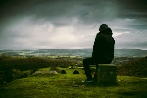 Man reflecting on a hill top