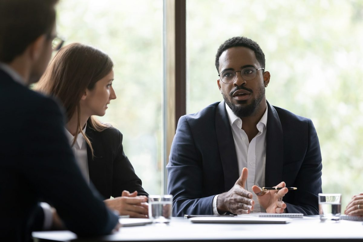 Concentrated black team leader posing problem to employees, afro-american coach or mentor setting target to group of trainees, manager discussing his business idea with diverse colleagues on meeting